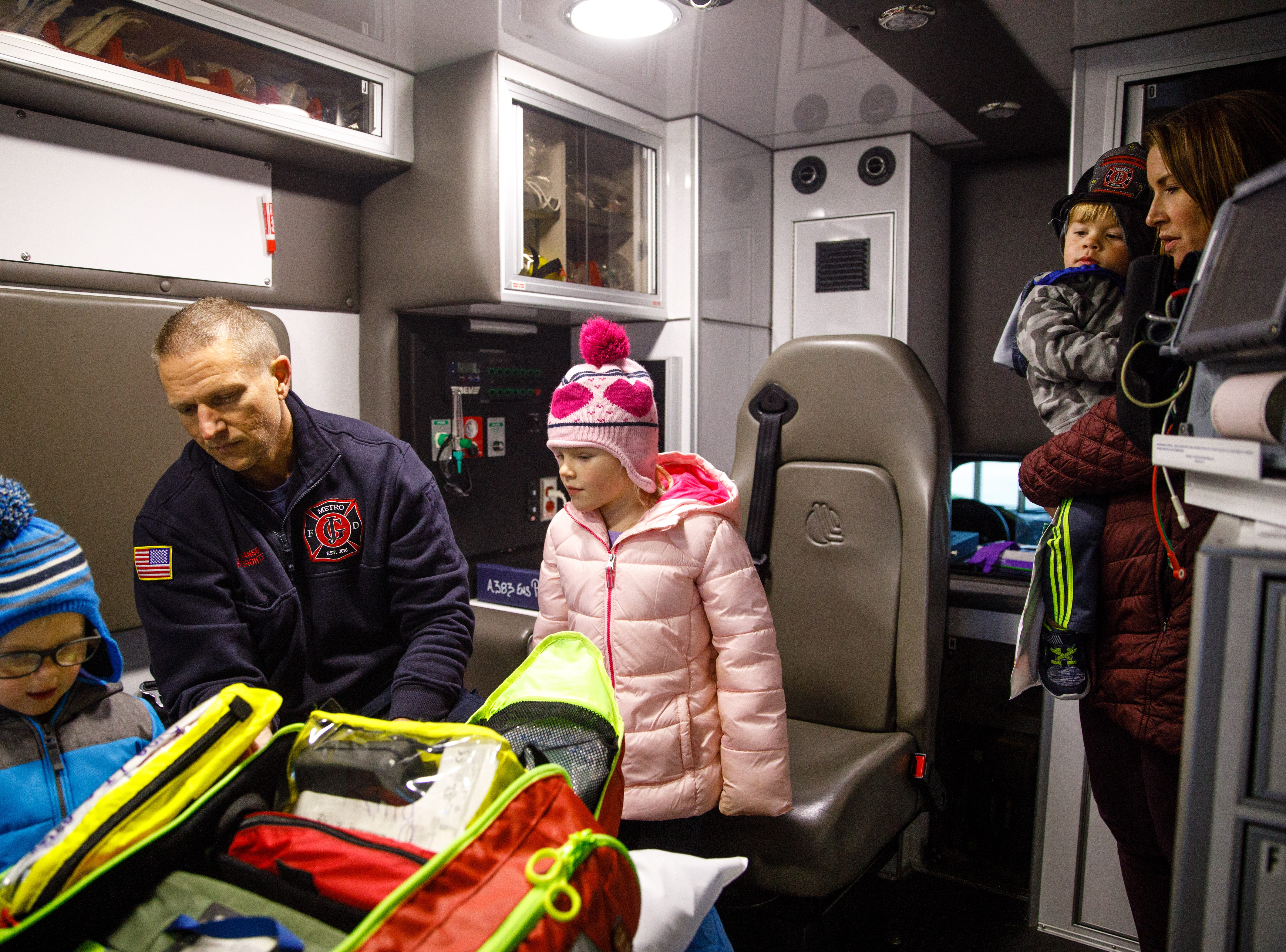 Firefighter/Paramedic Brook Hansen shows Braxton Lems, 3, and Sophie Lems, 4, both of Johnston, a kit of medical supplies as Laura Sprague and TJ Sprague, 2, both of Grimes, watch Wednesday, Oct. 10, 2018, during the Johnston-Grimes Metropolitan Fire Department's annual Fire Prevention Week Open House at the 62nd Avenue Fire Station in Johnston.
