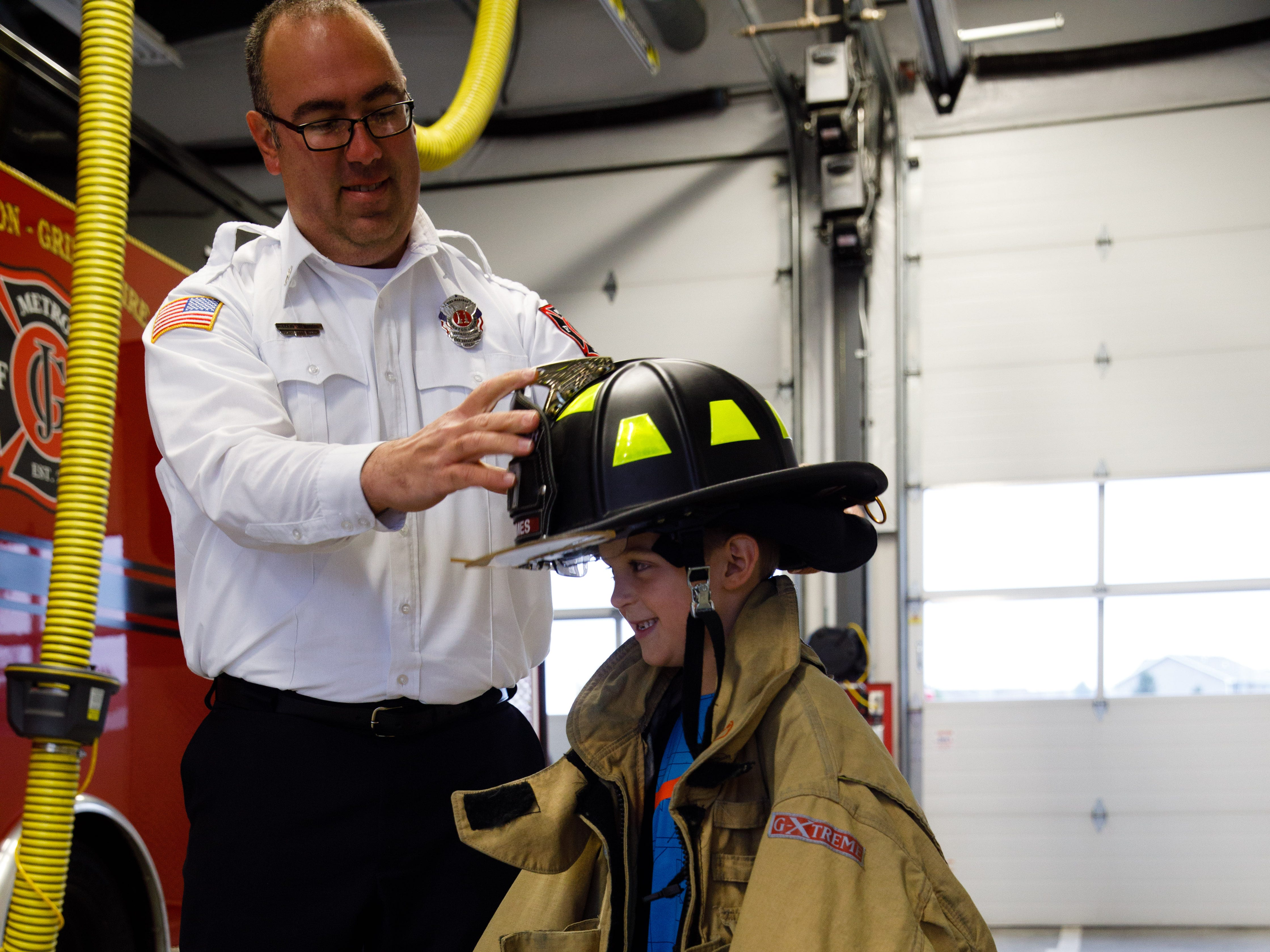 Fire Marshall Craig Van Huel helps Wyatt Puffer, 6, of Des Moines, put on firefighter protective gear Wednesday, Oct. 10, 2018, during the Johnston-Grimes Metropolitan Fire Department's annual Fire Prevention Week Open House at the 62nd Avenue Fire Station in Johnston.