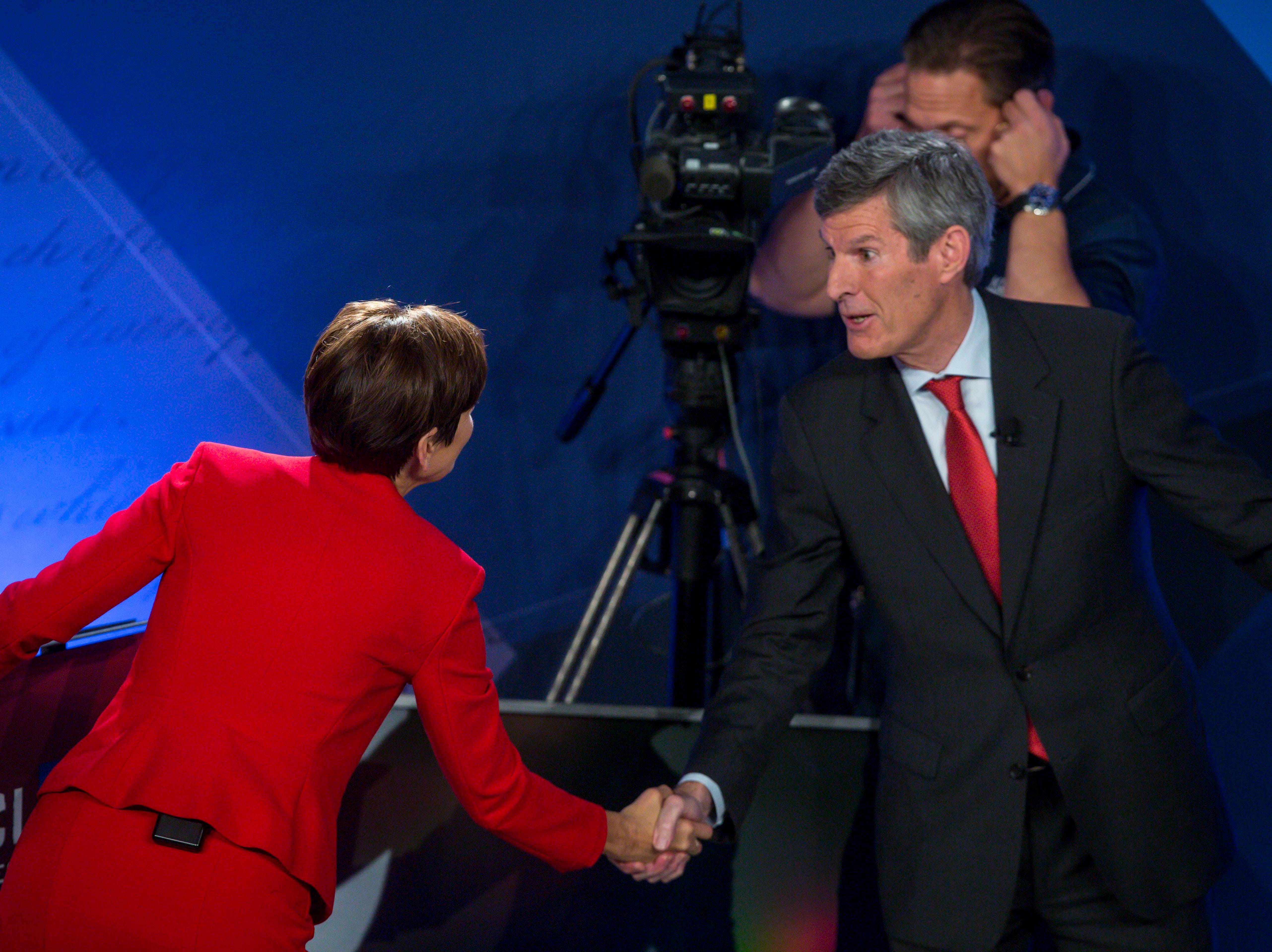 Republican Iowa Gov. Kim Reynolds and Democratic challenger Fred Hubbell shake hands after their debate Wednesday, Oct. 10, 2018, at Des Moines Area Community College in Ankeny, Iowa.