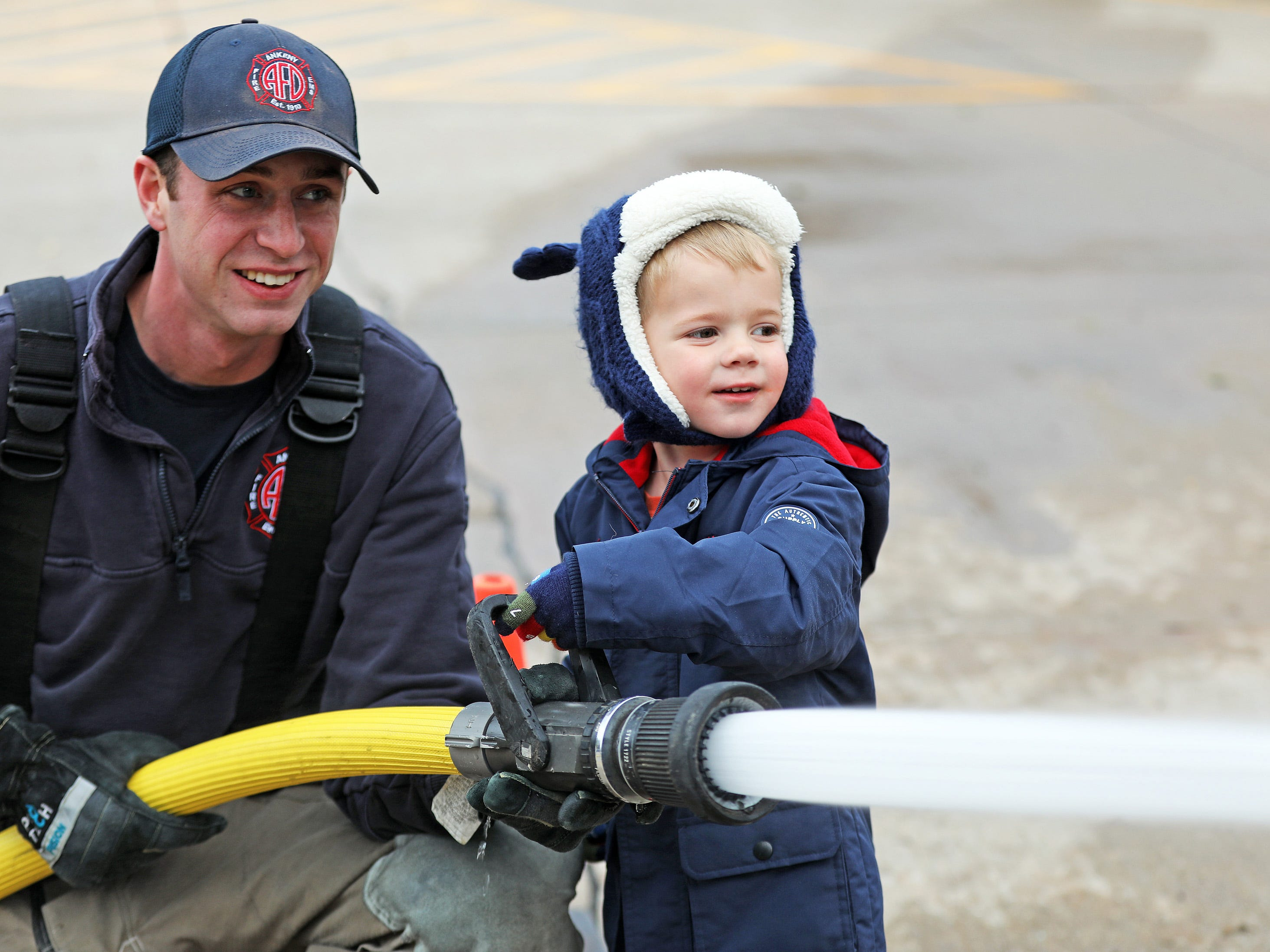 James Schleicher, 3, of Ankeny learns how to spray water on the target from Ankeny Firefighter Cole White during the Ankeny Fire Department's Fire Prevention Week Open House on Wednesday, Oct. 10, 2018 at Fire Station #1, 120 N.W. Ash Dr in Ankeny.