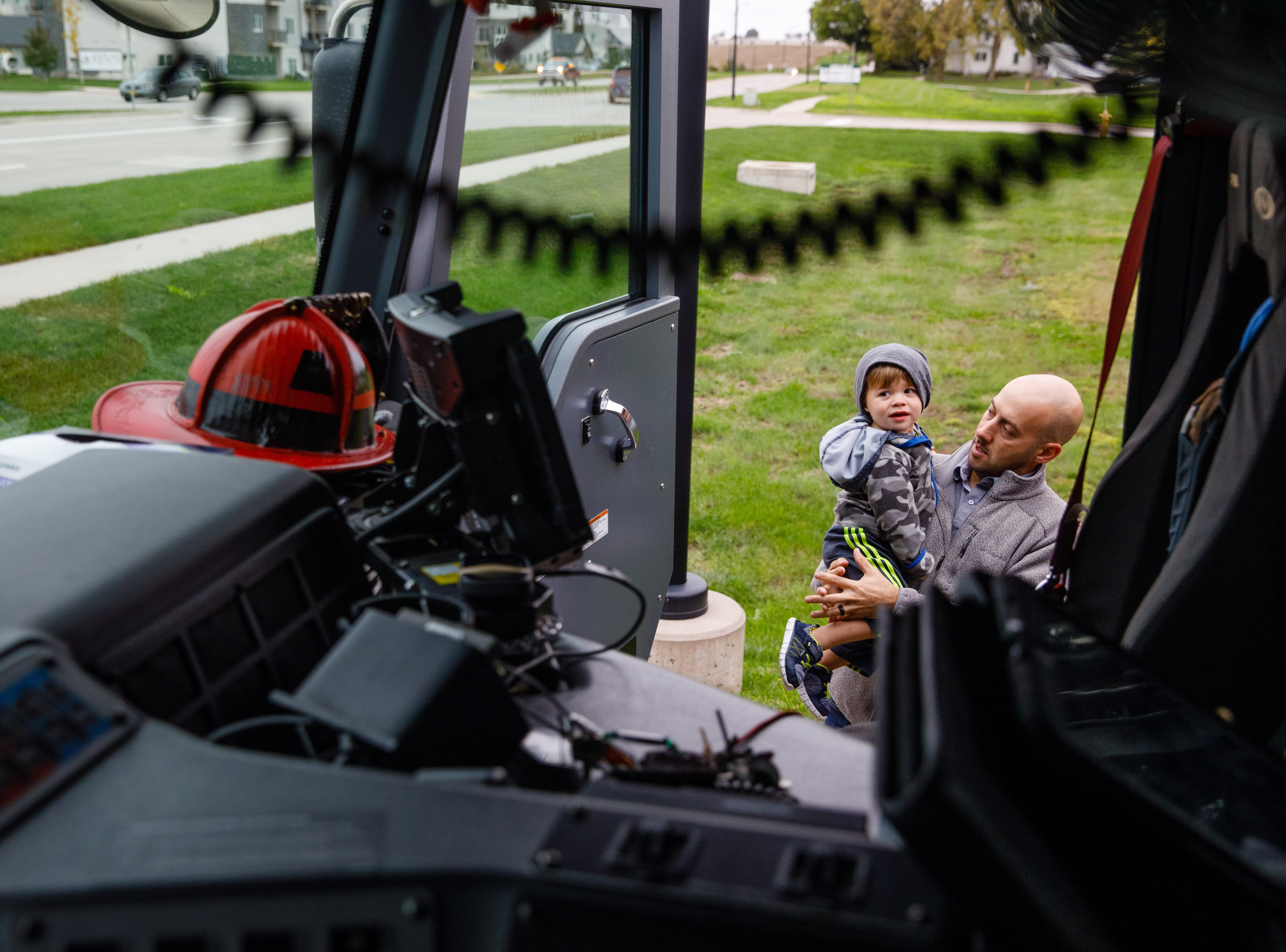 TJ Sprague, 2, and Joshua Sprague, both of Grimes, look into a fire truck Wednesday, Oct. 10, 2018, during the Johnston-Grimes Metropolitan Fire Department's annual Fire Prevention Week Open House at the 62nd Avenue Fire Station in Johnston.