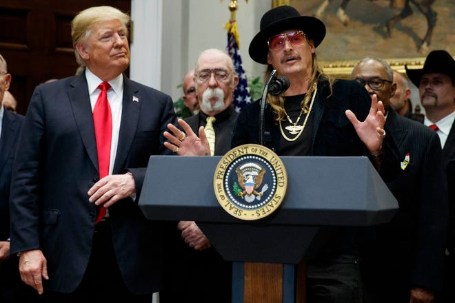 """President Donald Trump looks on as musician Kid Rock speaks during a signing ceremony for the """"Orrin G. Hatch-Bob Goodlatte Music Modernization Act,"""" at the White House, Thursday, Oct. 11, 2018, in Washington."""