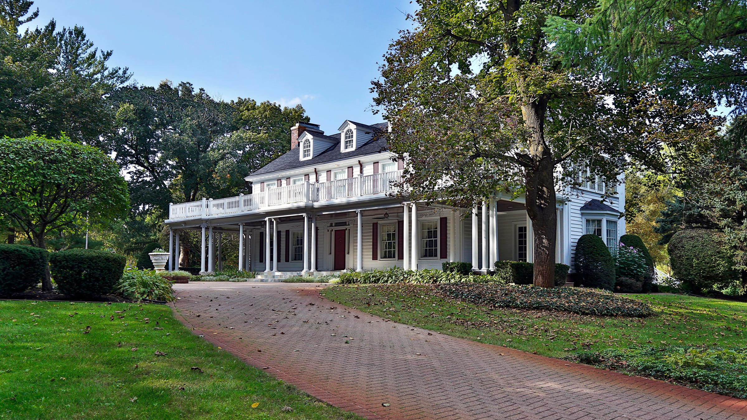 """Landmark house on the border of Novi and Northville has been home to a succession of entrepreneurs, including the late """"Cadillac King"""" Don Massey. The long colonnade style porch has a second-floor veranda above."""