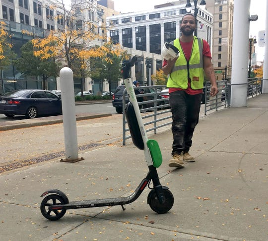Chris Rogers, 27, of Taylor, approaches a Lime scooter outside the downtown YMCA in Detroit on Wed., Oct. 10, 2018.