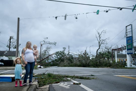 """A woman and her children wain near a destroyed gas station after Hurricane Michael in Panama City, Florida on October 10, 2018. - Michael slammed into the Florida coast on October 10 as the most powerful storm to hit the southern US state in more than a century as officials warned it could wreak """"unimaginable devastation."""" Michael made landfall as a Category 4 storm near Mexico Beach, a town about 20 miles (32kms) southeast of Panama City, around 1:00 pm Eastern time (1700 GMT), the National Hurricane Center said."""