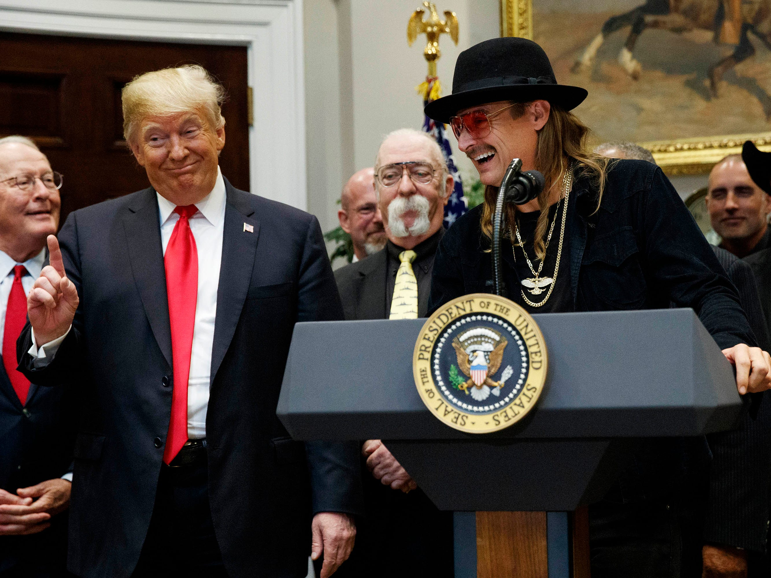 "President Donald Trump gestures as musician Kid Rock speaks during a signing ceremony for the ""Orrin G. Hatch-Bob Goodlatte Music Modernization Act,"" at the White House, Thursday, Oct. 11, 2018, in Washington."