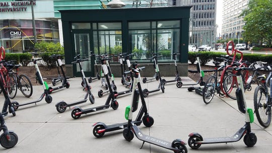 There are many parked scooters in downtown outside Chase Tower in downtown Detroit on Wed., Oct. 10, 2018.