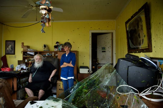"""Charles Swaney (L) sits in a motel office after Hurricane Michael October 10, 2018 in Panama City, Florida. - Michael slammed into the Florida coast on October 10 as the most powerful storm to hit the southern US state in more than a century as officials warned it could wreak """"unimaginable devastation."""" Michael made landfall as a Category 4 storm near Mexico Beach, a town about 20 miles (32kms) southeast of Panama City, around 1:00 pm Eastern time (1700 GMT), the National Hurricane Center said."""