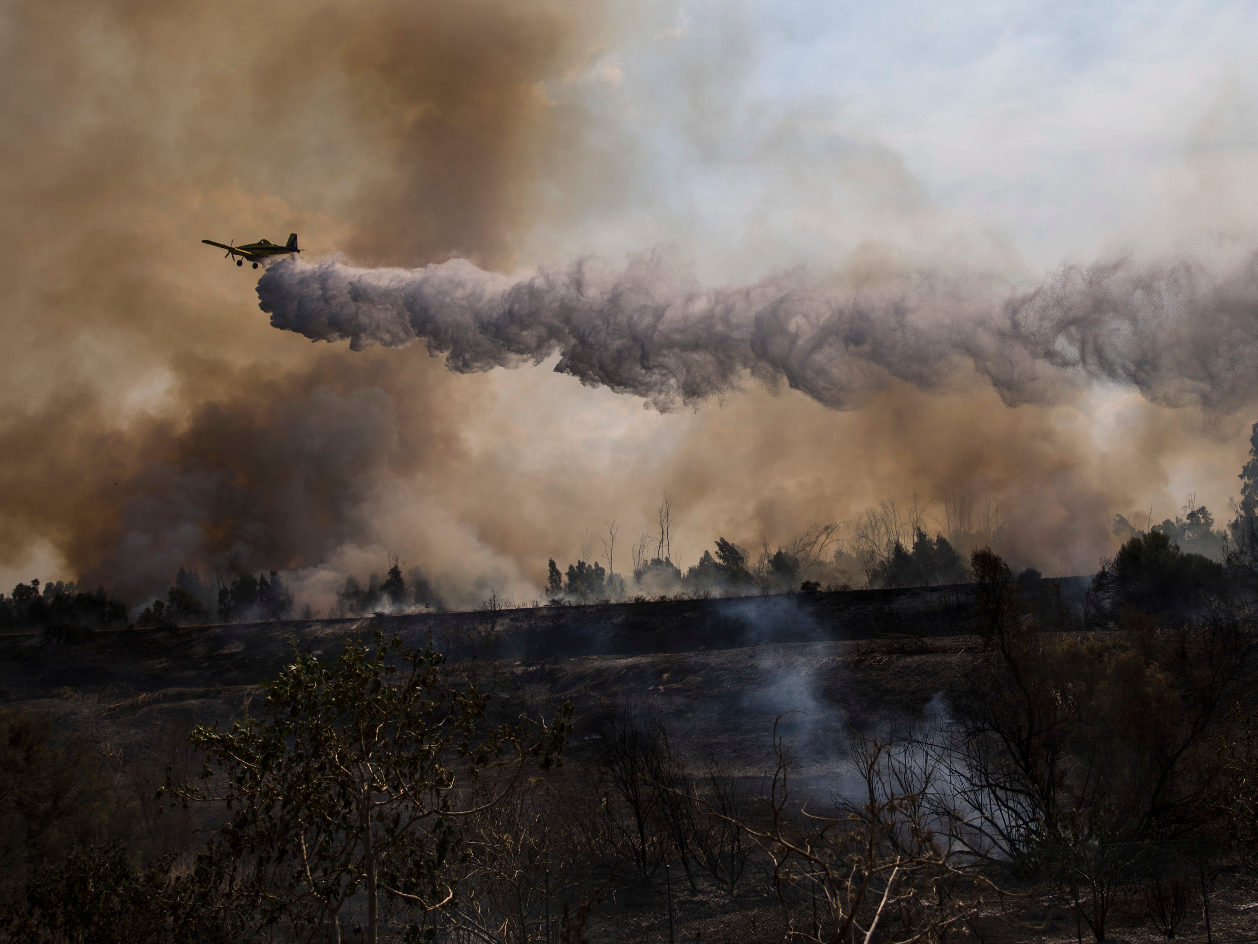A firefighting plane passes over a fire started by a balloon with attached burning cloth launched by Palestinians from Gaza Strip in Karmia nature reserve park near the Israel and Gaza border, Thursday, Oct. 11, 2018.