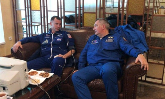 NASA Astronaut Nick Hague, left, and Roscosmos Director Dmitry Rogozin sit in Dzhezkazgan, Kazakhstan on Thursday, Oct. 11, 2018, after an emergency landing following the failure of a Russian booster rocket carrying them to the International Space Station.