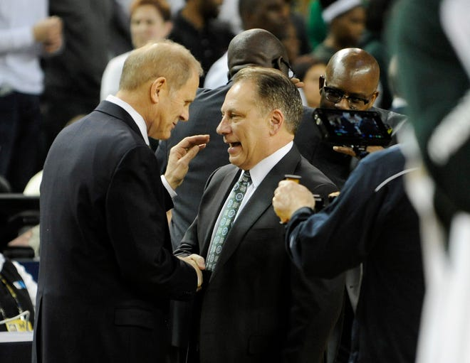 Michigan head coach John Beilein, left, and Michigan State coach Tom Izzo will square off twice during the regular season under the Big Ten's new 20-game schedule.