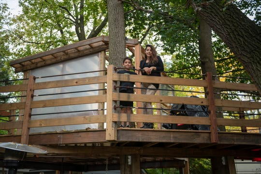 Tamar Boyadjian and her seven-year-old son Daniel Avedissian stand in their backyard treehouse at their Ann Arbor home, October 10, 2018. The family is in a battle with the city on the construction of the treehouse.