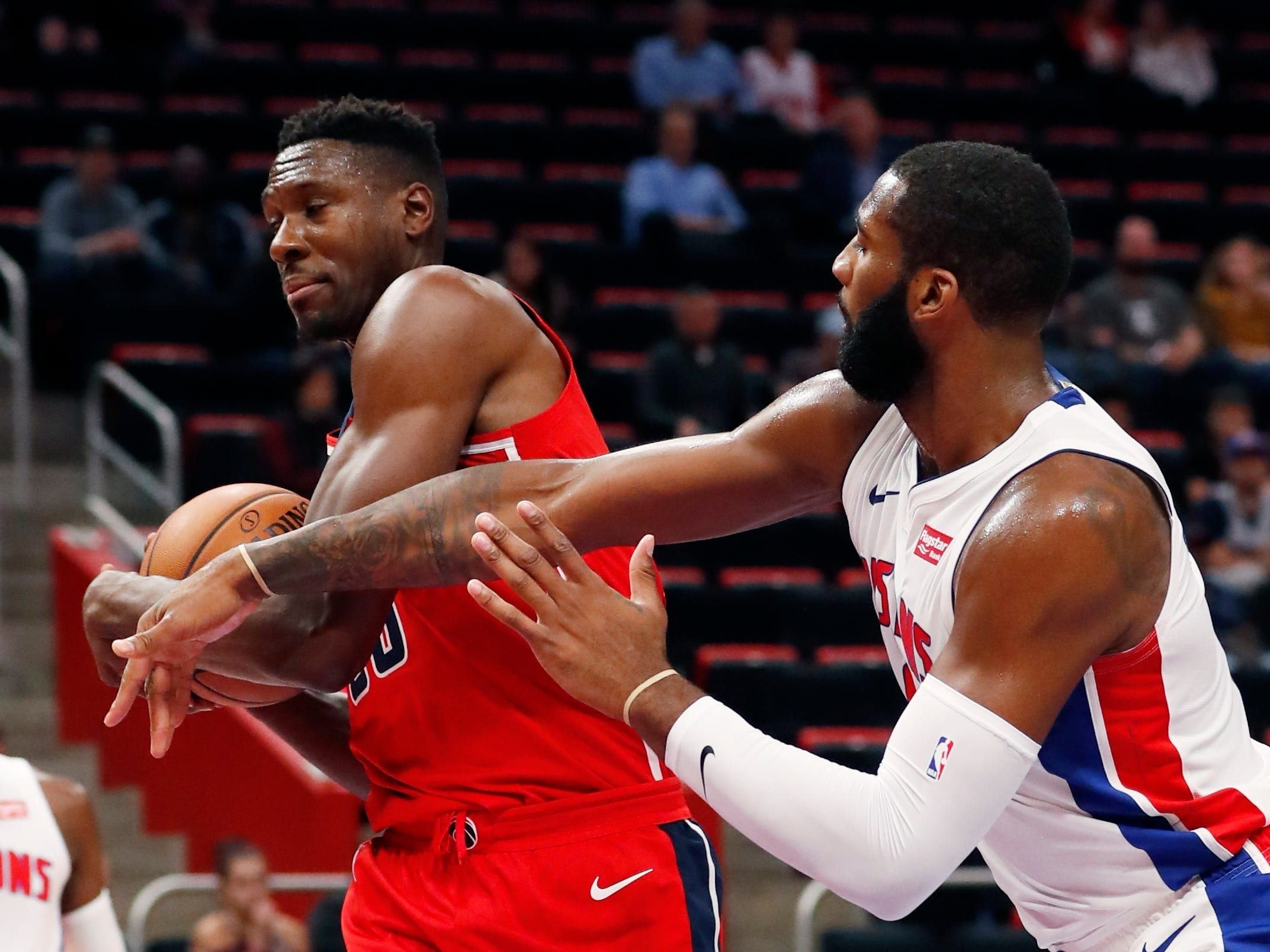 Detroit Pistons center Andre Drummond, right, reaches in as Washington Wizards center Ian Mahinmi grabs a rebound during the first half.