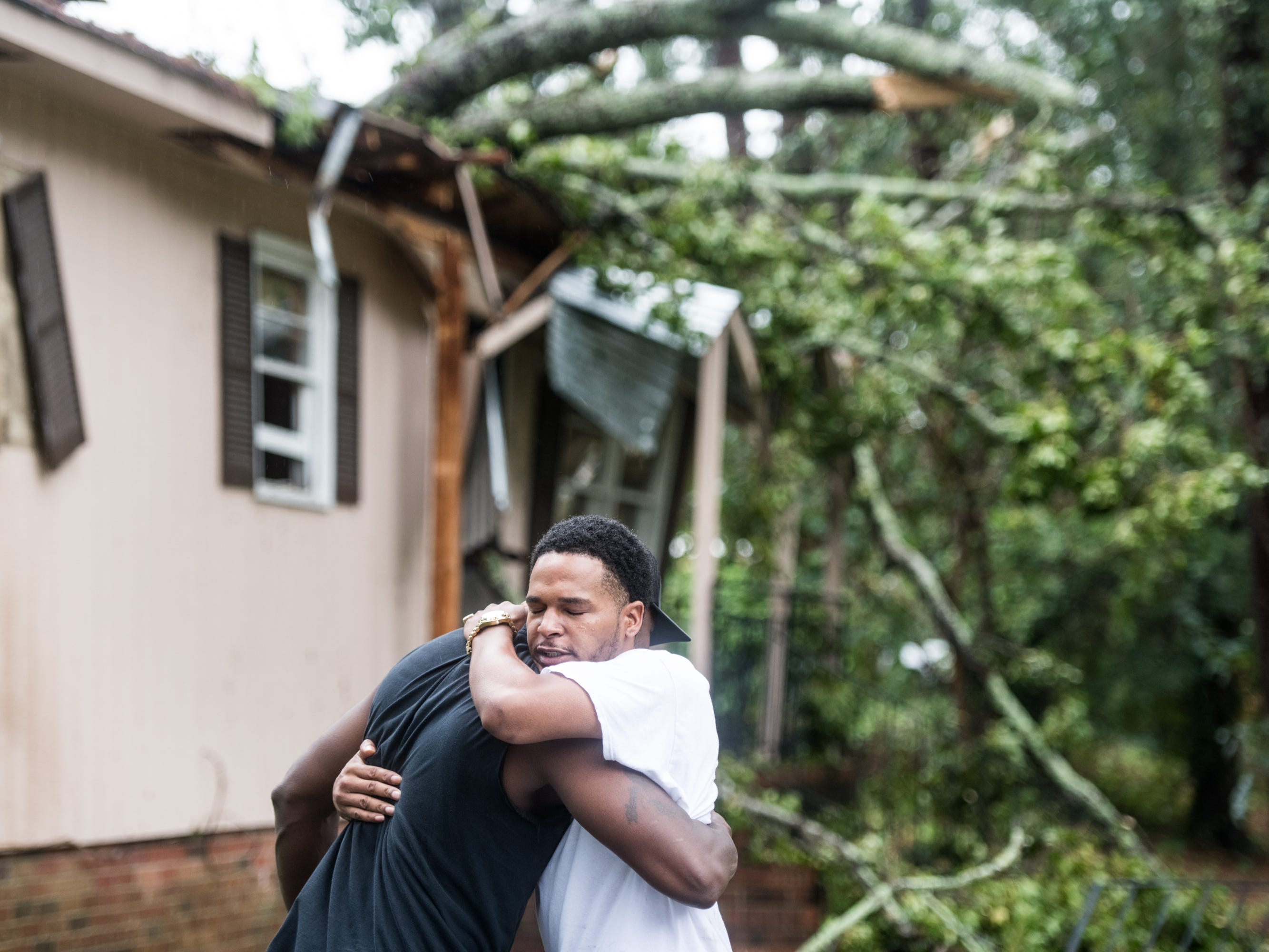 Hector Benthall, right, gets a hug from his neighbor Keito Jordan after remnants of Hurricane Michael sent a tree crashing into Benthall's home on Oct. 11, 2018 in Columbia, South Carolina. Jordan was the first responder to the accident that sent at least one person to the hospital.