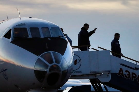 U.S. astronaut Nick Hague, center, and Russian cosmonaut Alexey Ovchinin, right, arrive in Baikonur airport, Kazakhstan, Thursday, Oct. 11, 2018.