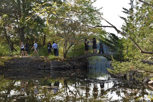 Guests enjoy the newly refurbished Lily Pond Cascade, unveiled during a ceremony Tuesday at the Cranbrook Japanese Garden.