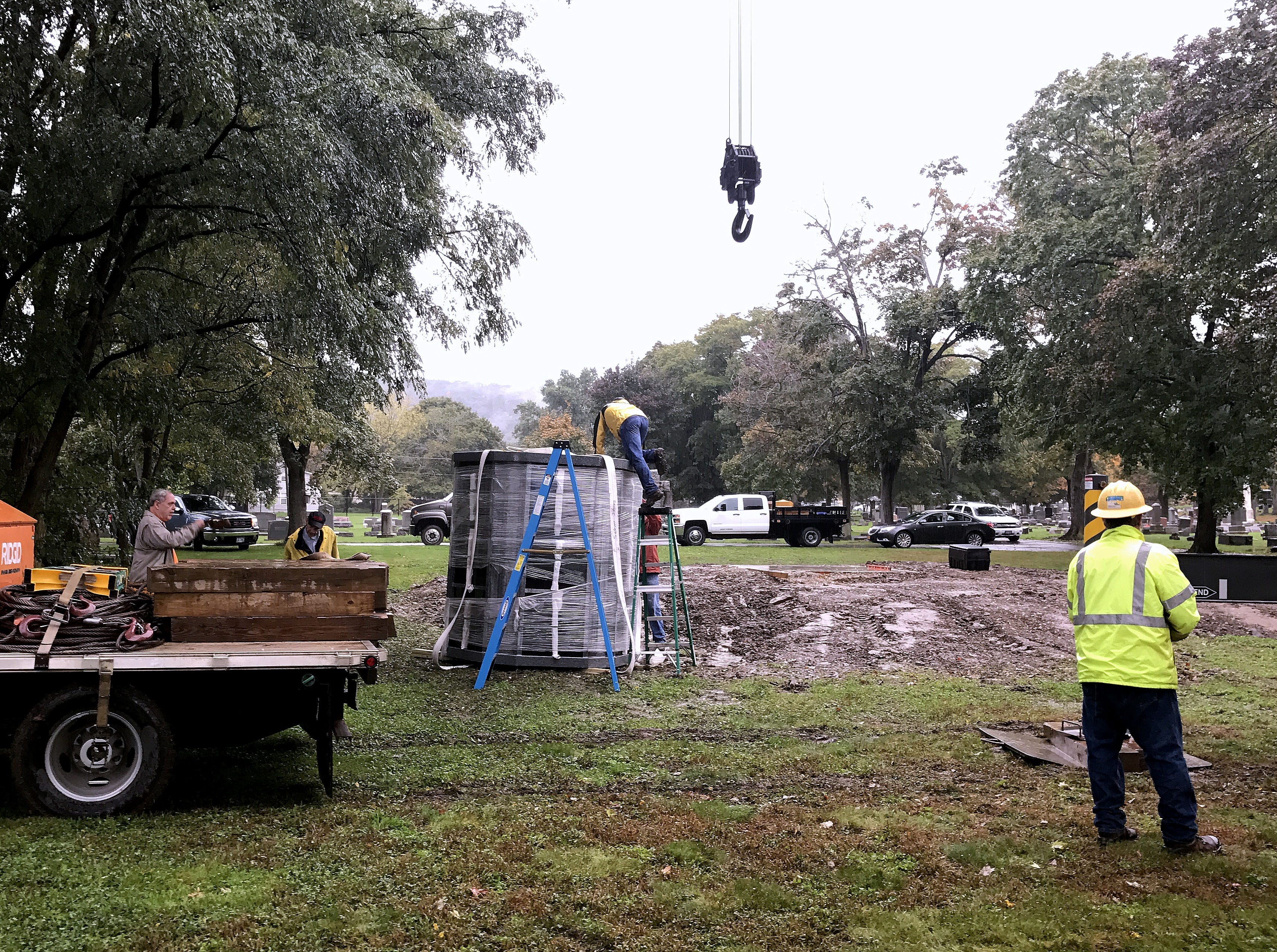 A crane sets a columbarium down temporarily Thursday as crews prepare to move it to a platform at Woodlawn Cemetery in Elmira.