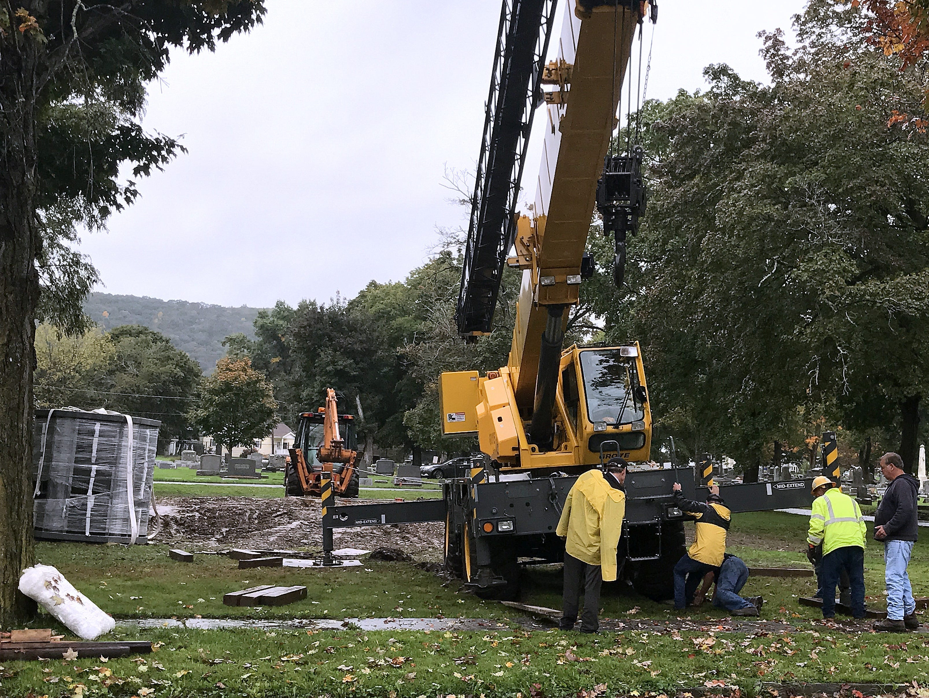A crane gets stuck in mud while moving a 9-ton columbarium Thursday at Woodlawn Cemetery.