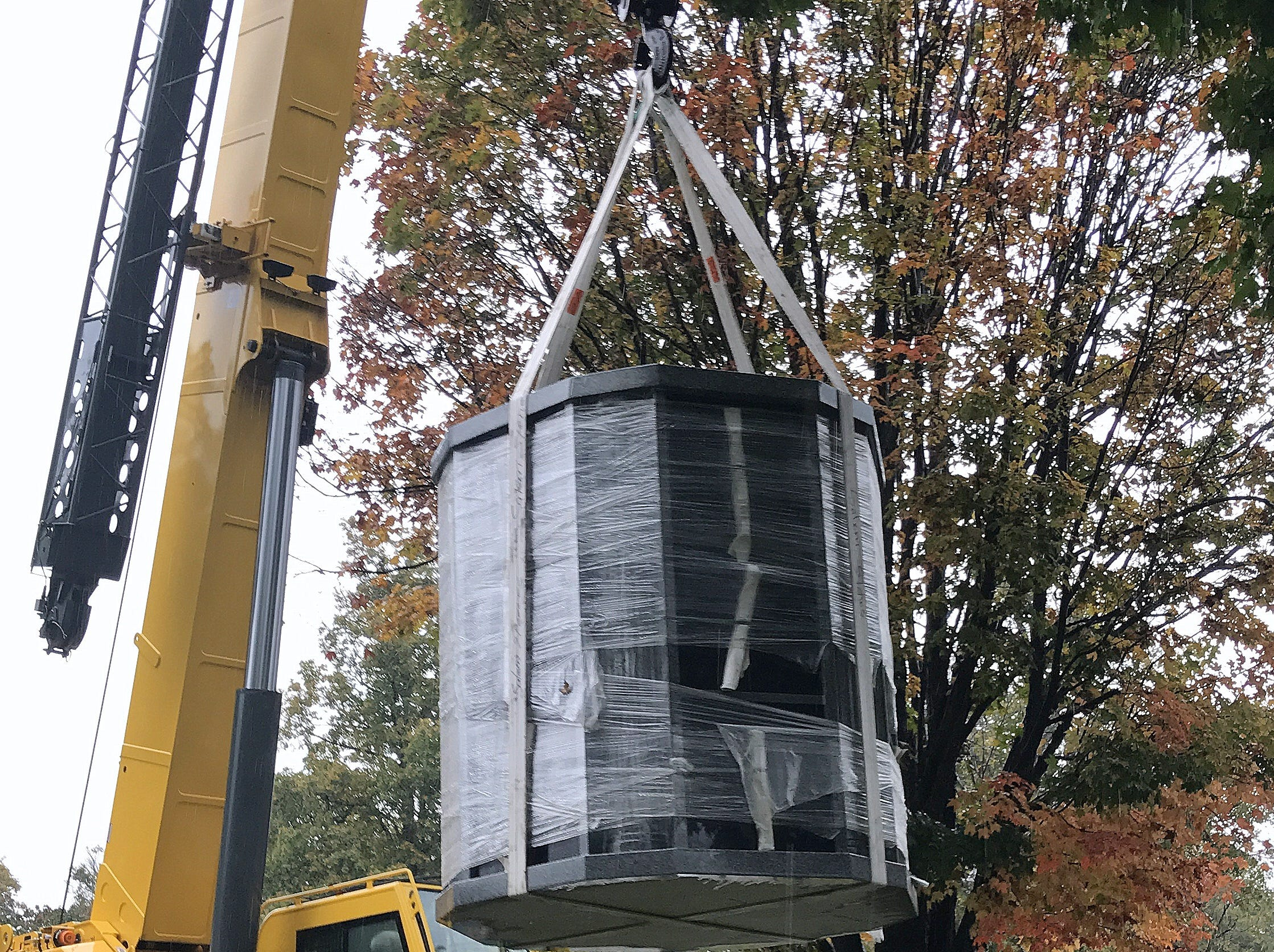A crane swings a columbarium designed to hold cremated remains off a truck Thursday at Woodlawn Cemetery.