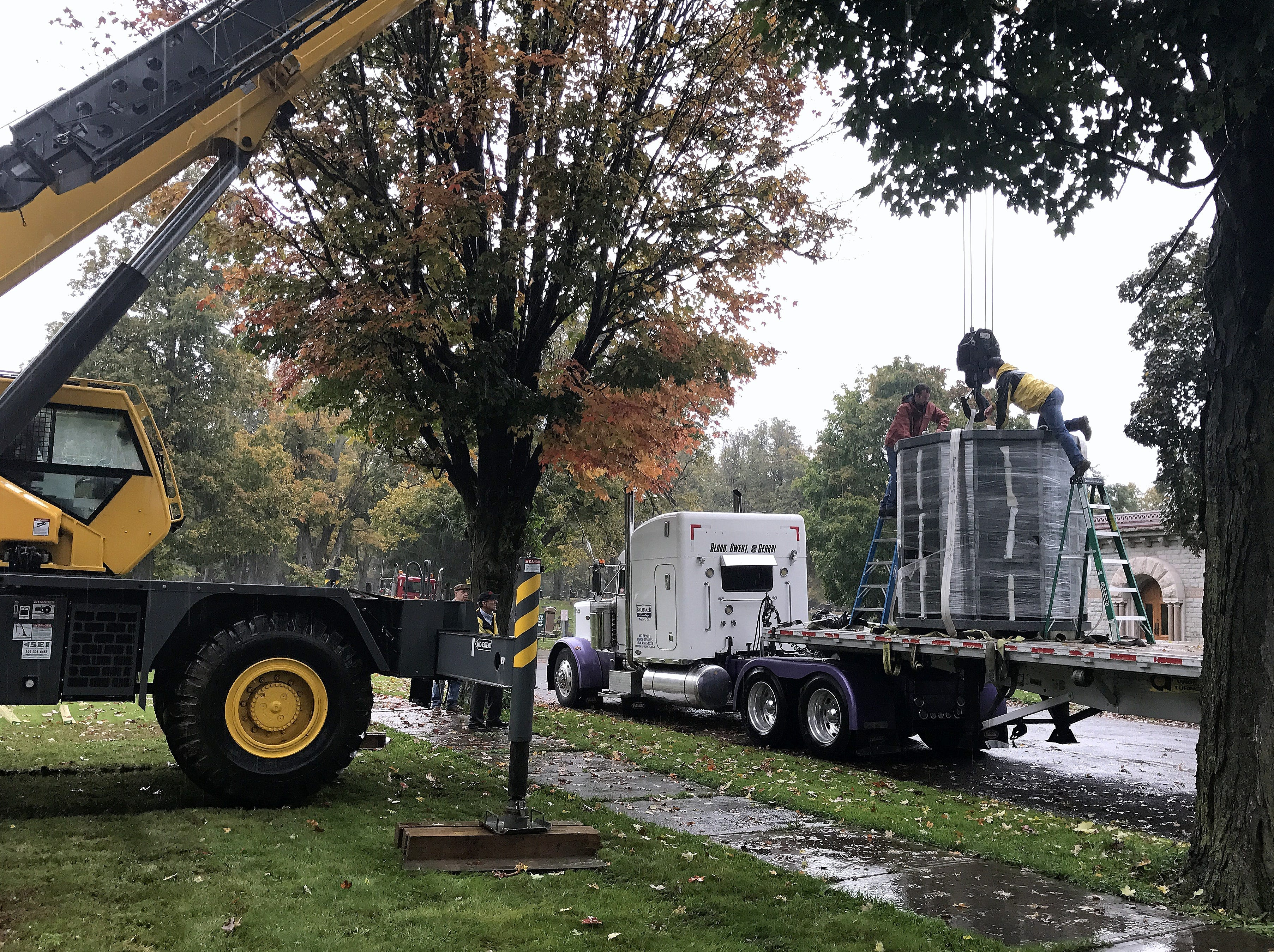 A crew hooks a 9-ton columbarium to a crane Thursday at Woodlawn Cemetery in Elmira.