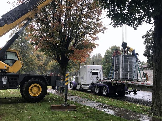 A crew hooks a 9-ton columbarium to a crane Thursday at Woodlawn Cemetery in Elmira.