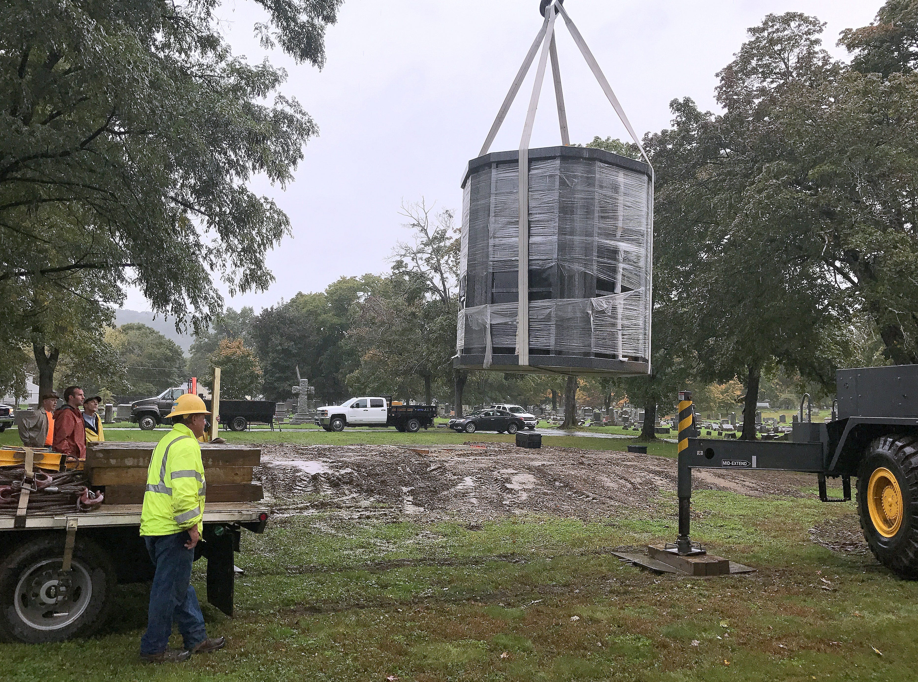 A new columbarium is hoisted toward a platform at Woodlawn Cemetery.