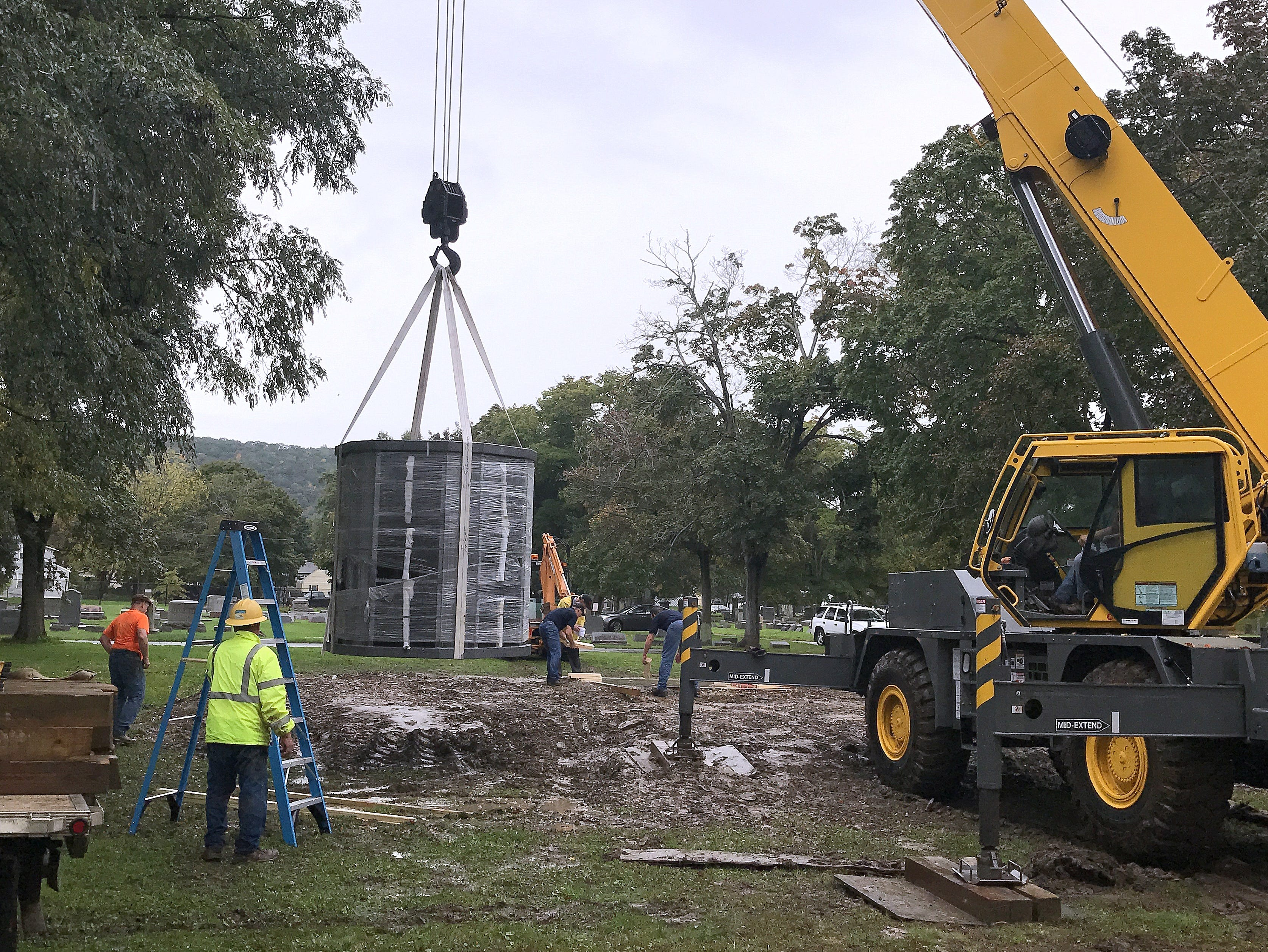 A crane lifts a 9-ton columbarium off the ground Thursday as it prepares to move it to a platform at Woodlawn Cemetery.