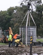Final adjustments are made as a crane prepares to lower a 9-ton columbarium onto a platform at Woodlawn Cemetery.