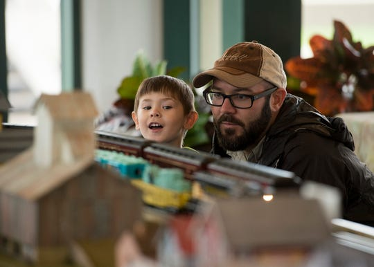 Henry Gish, 3, and John Gish enjoy the afternoon looking at trains during the Local Loco Model Railroad Club show at the Evansville Pagoda Sept. 22, 2018.