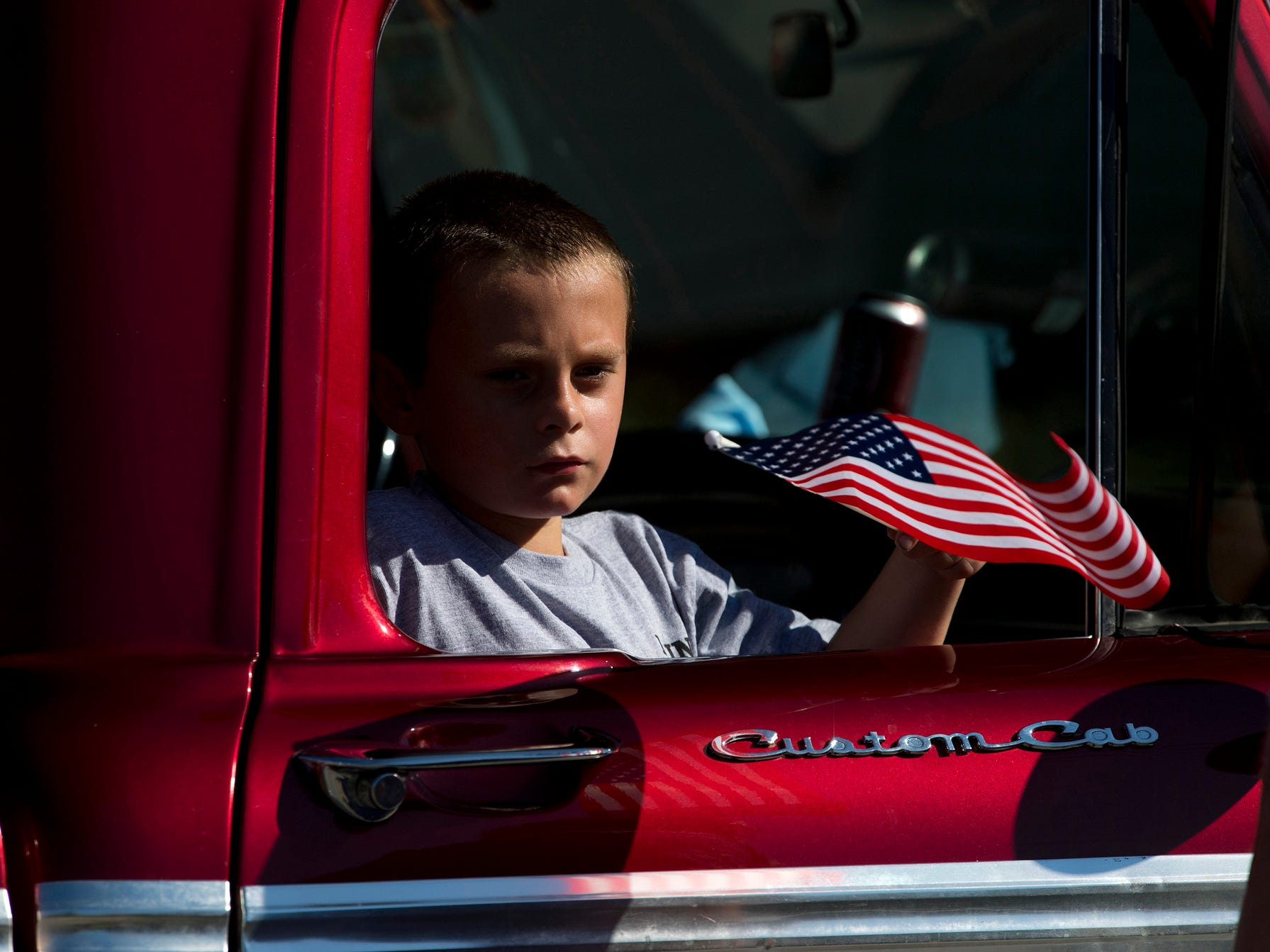 Ethan Bailey, 7, of Centralia, Ill., hitches a ride in a '66 Ford pickup driven by Bob Galloway of Lynnville, Ind.,at the 132nd Annual Labor Day Celebration in Boonville, Ind., Monday morning, September 3, 2018. They were representing the Laborers Local 561.