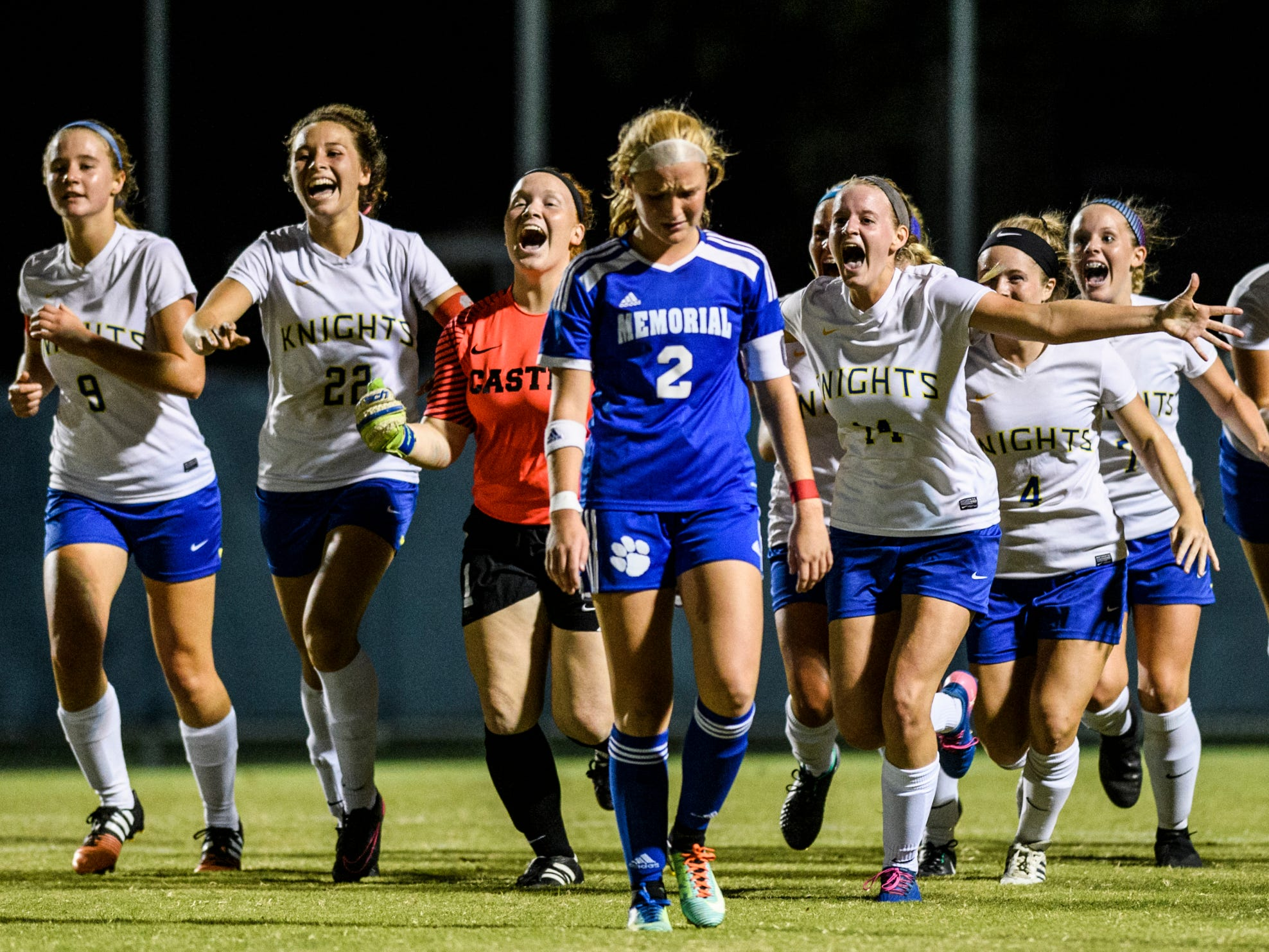 The Castle Knights celebrate their victory as the game clock runs out and Memorial's Isabel Alexander (2) walks back to her team at Traylor Family Stadium in Evansville, Ind., Tuesday, Sept. 11, 2018. The Knights remain undefeated after a 2-1 victory over the Tigers.