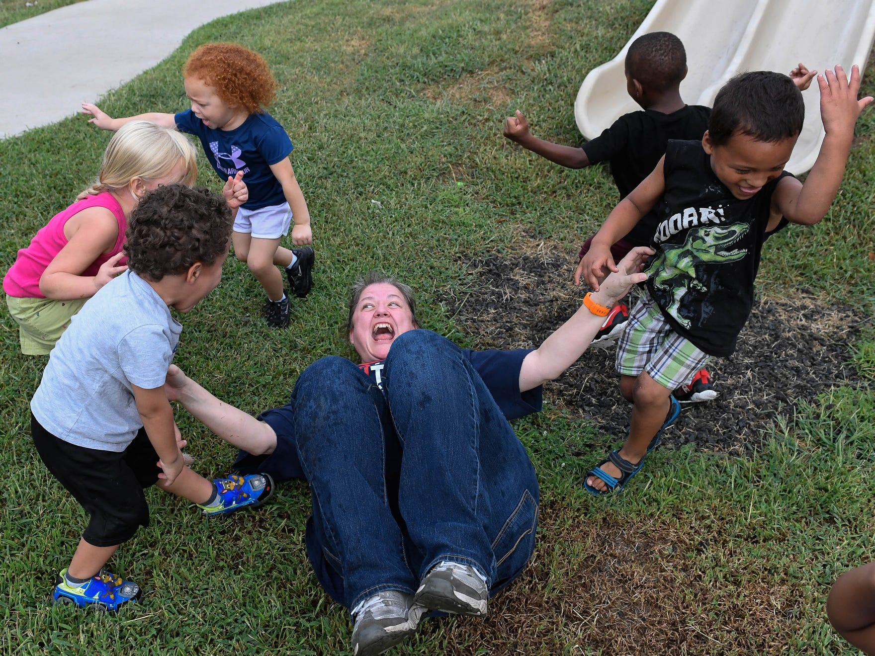 Vectren volunteer Fauna Kell gets down in the grass to play zombies with kids at the Ark Crisis Child Care for the United Way Day of Caring, where hundreds of volunteers spend the day working at local nonprofit agencies to kick off the annual United Way fall campaign Friday, September 7, 2018.