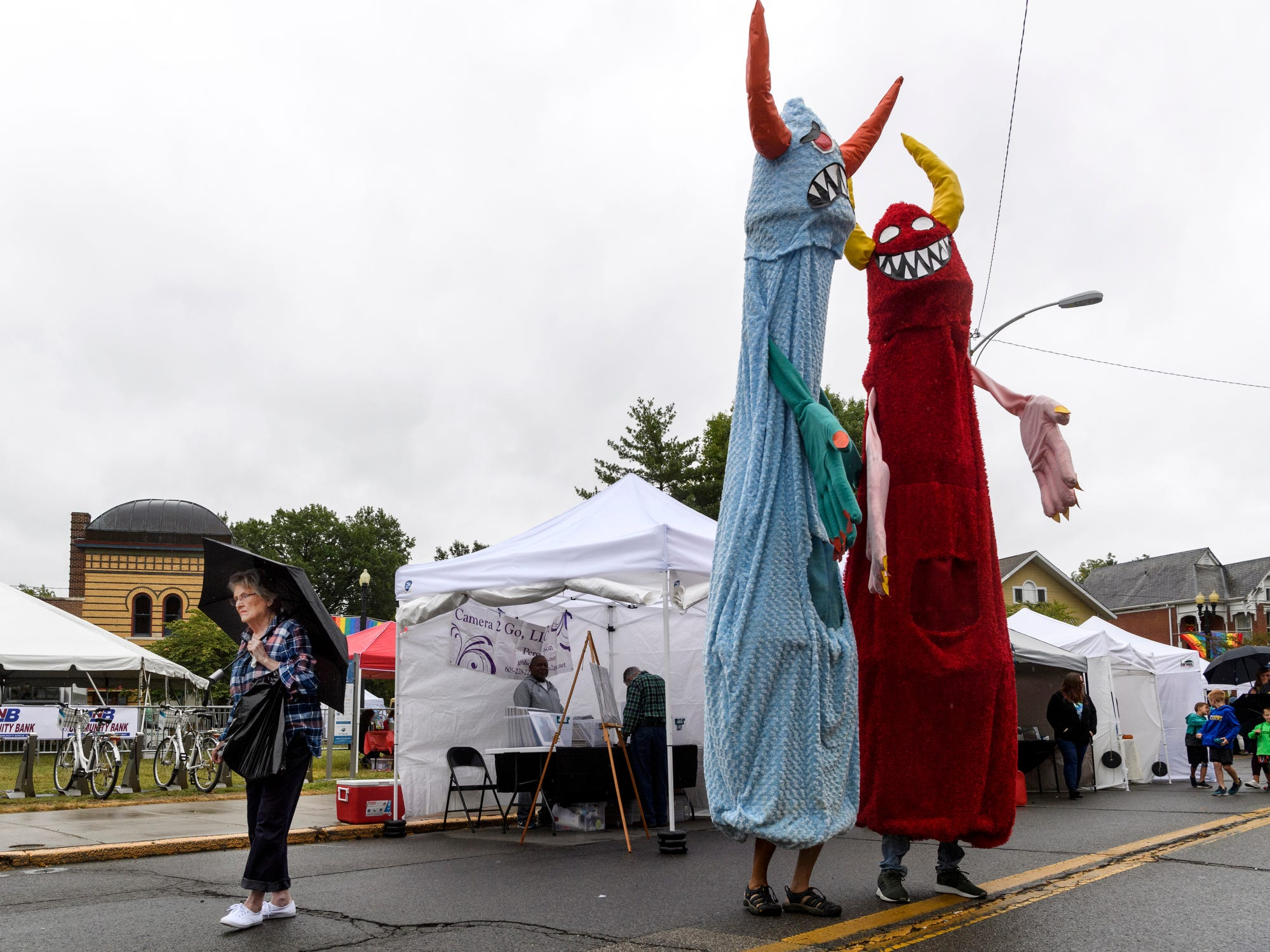 Lynne Mowrey, from left, browses booths as Warren Hayes and his son Chauncey Hayes greet people in monster costumes at the Fall Funk in the City Art Festival set up around Haynie's Corner in Evansville, Ind., Saturday, Sept. 22, 2018. A steady crowd of people braved periodic rain and cooler temperatures to purchase art and food from local vendors.