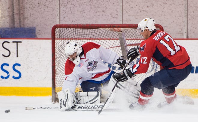 UNITED STATES - MARCH 25: Lobbyist goalie Brian Regan, of the FCC, blocks a shot from former Capitals star and current Lawmakers forward Peter Bondra during the 7th Annual Congressional Hockey Challenge at the Kettler Capitals Iceplex in Arlington, Va., on Wednesday, March 25, 2015. Rep. Katko fired the rebound into the net for the winning goal. The Lawmakers defeated the Lobbyists 3-2. (Photo By Bill Clark/CQ Roll Call) (CQ Roll Call via AP Images)