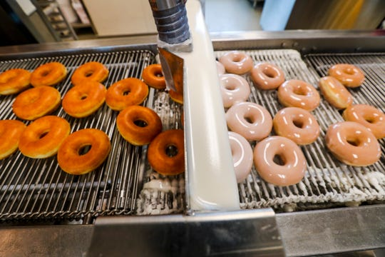Doughnuts pass under a cascade of glaze at the new Krispy Kreme in Fort Myers. The store opens to the public Tuesday.