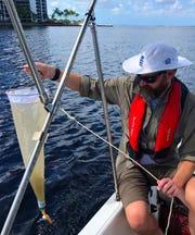 Algae researcher James Metcalf samples the Caloosahatchee for toxic cyanobacteria.