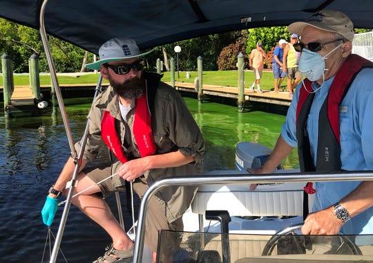 Researcher James Metcalf, left samples for toxic algae as Calusa Waterkeeper John Cassani pilots a boat through the Caloosahatchee's cyanobacteria bloom