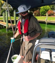 Researcher James Metcalf pulls up a sample of water from a North Fort Myers canal. He was on the Caloosahatchee researching toxic blue-green algae (cyanobacteria) that's been blooming in the river since June.