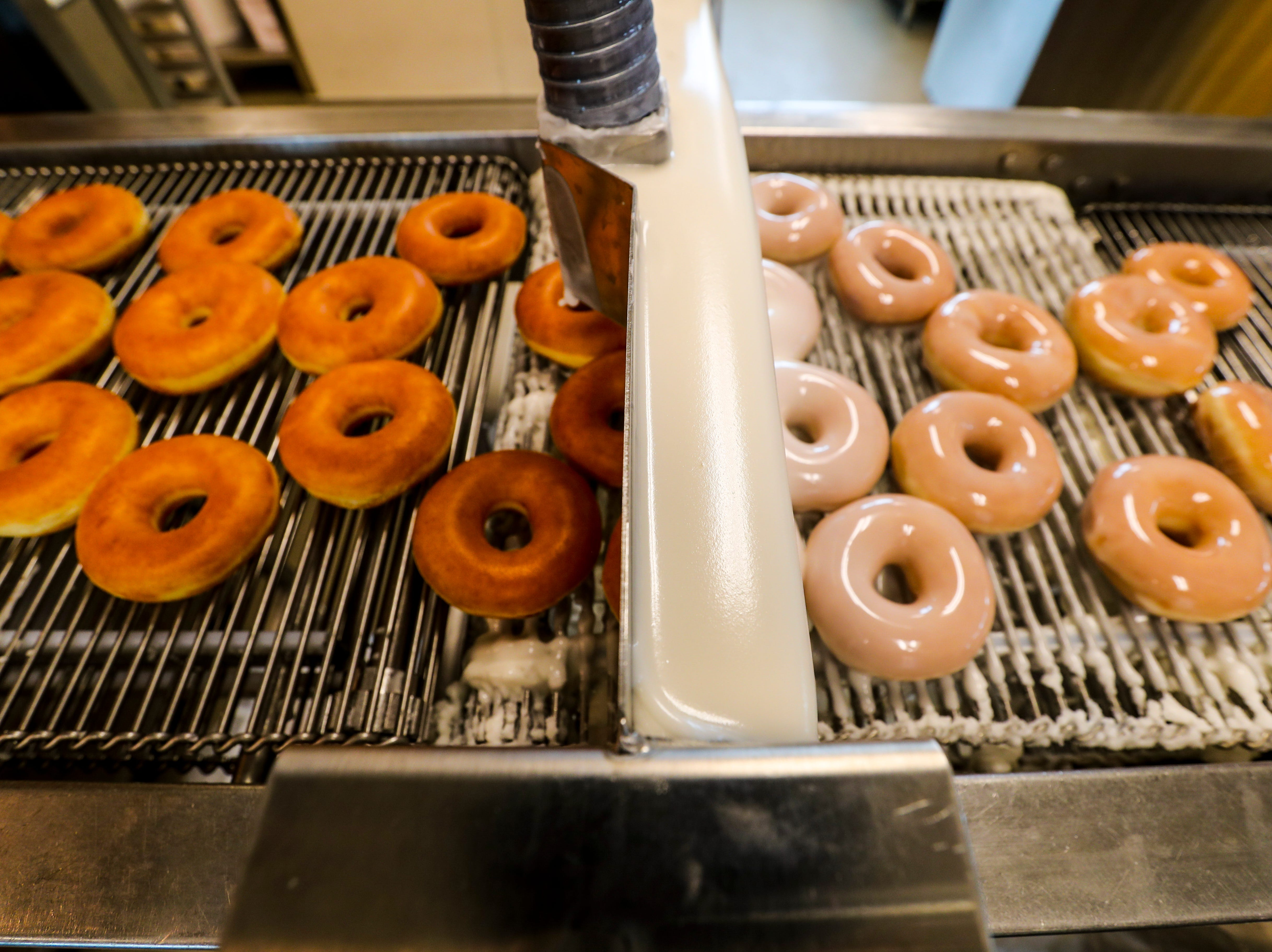 The workers who will make the Krispy Kreme doughnuts daily have been practicing up. The doughnuts start from freshly made dough, that is placed into a  machine that forms it into doughnuts, then to the proofer for a little over a half hour. Once they are ready the fluffy dough is flipped into oil and then flipped to the other side, leaving the signature white ring. The signature Krispy Kreme doughnut is then iced and boxed up hot and ready. The store will open in five days. October 11, 2018.