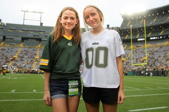 """Myah Mlnarik and Hayden Beekman  pose for a photo at the Aug. 16 on the sidelines of Lambeau Field. Because of their Bundles of Hope project, they were  selected by ShopKo and the Packers as """"Kic-Ooff Kids,"""" to run onto on the field and retrieve the kicking tee the game."""
