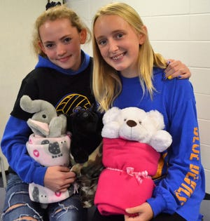 Myah Mlnarik and Hayden Beekman , seventh graders at Bayshore Community Academy in Oconto, hold two of their Bundles of Hope. For two years, they have made handed out bundles of a stuffed animal, blanket and inspirational message to people of all ages going through difficult times.