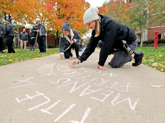 St. Norbert College student and campus Equality Project president Sarah Chojnacki, right, and Neale Tracy use chalk to write what Titles IX means to them at a rally to focus attention on Title IX issues at the school Thursday in De Pere.