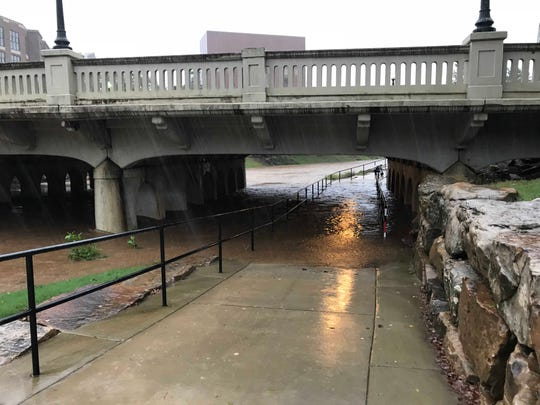 The Reedy River overflows onto the Swamp Rabbit Trail at the River Street overpass in downtown Greenville on Thursday, Oct. 11, 2018, after heavy rains triggered by Tropical Storm Michael lashed the Upstate.