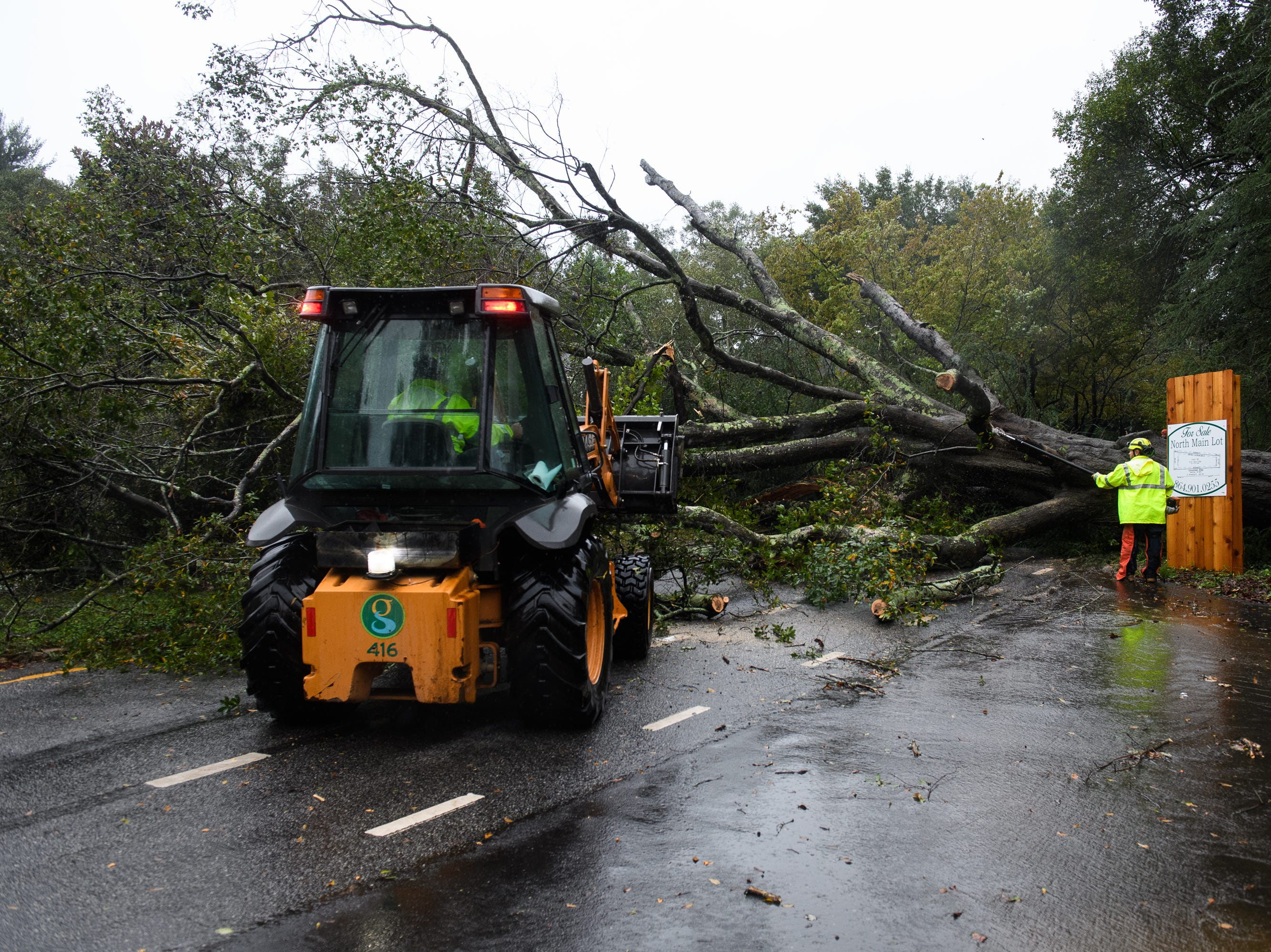 A worker begins to cut down a tree that fell on North Main Street as Tropical Storm Michael hits the Greenville area on Thursday, Oct. 11, 2018.