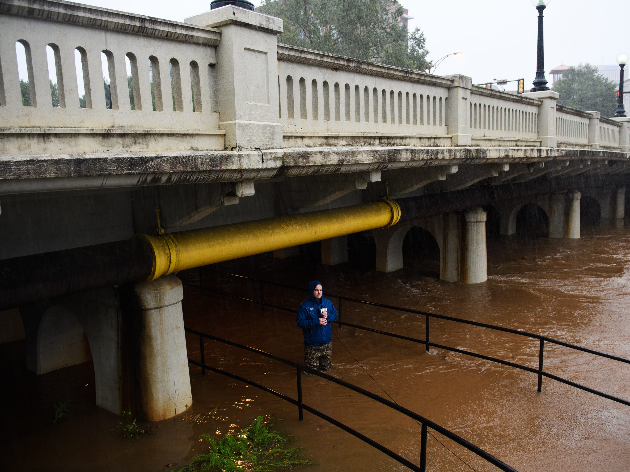 A local television reporter stands in flood water along the Swamp Rabbit Trail in downtown Greenville as Tropical Storm Michael hits the area on Thursday, Oct. 11, 2018.