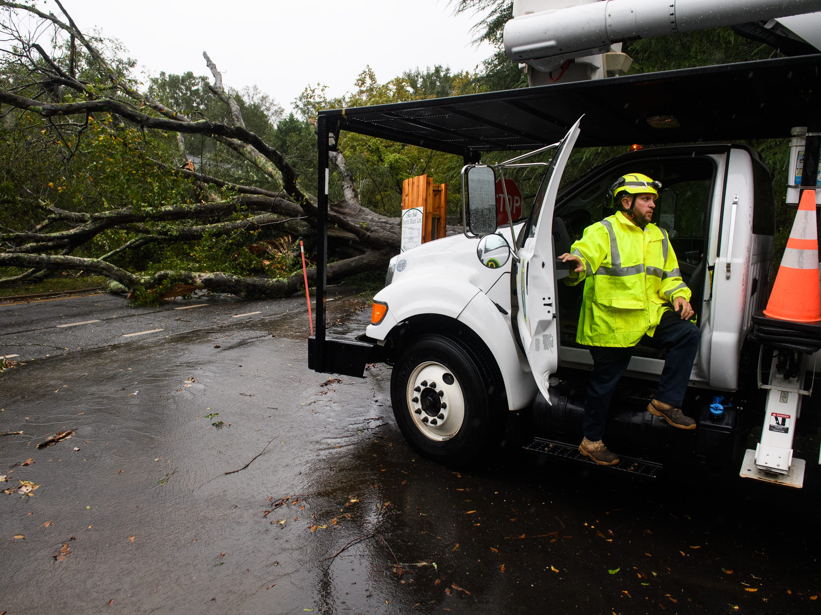 A worker responds to a down tree on North Main Street as Tropical Storm Michael hits the Greenville area on Thursday, Oct. 11, 2018.