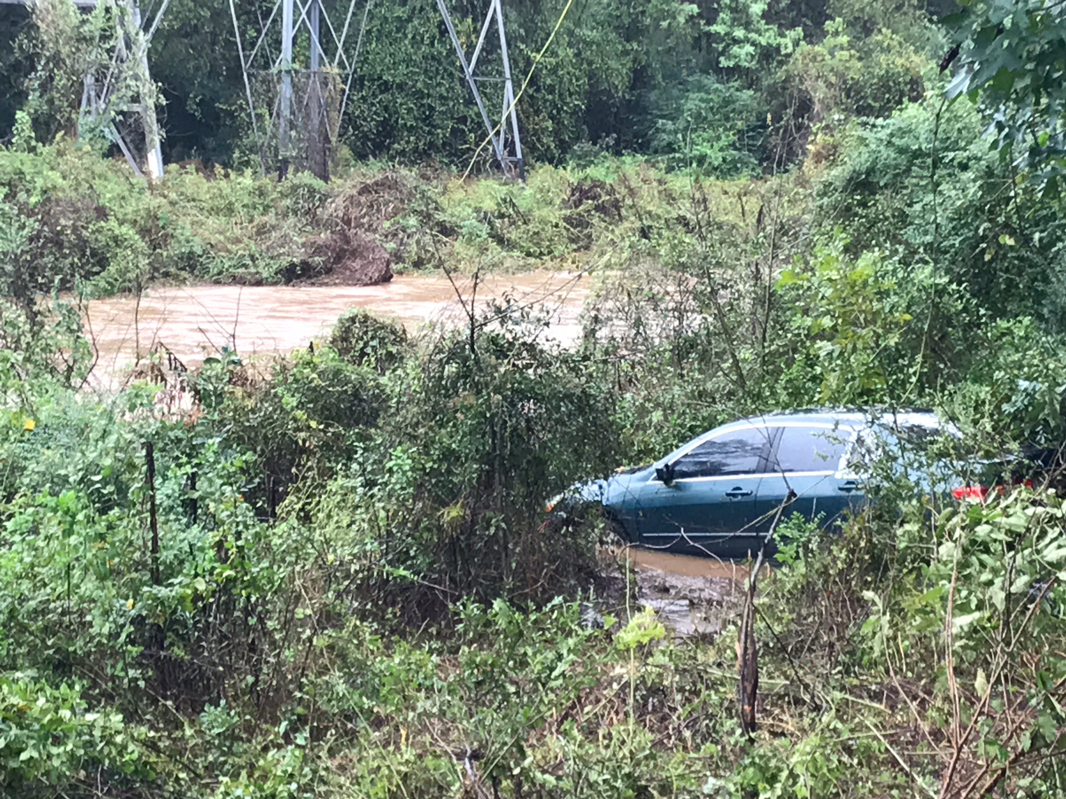 An unoccupied car is partially submerged off Parkins Mill Road  in Greenville on Thursday, Oct. 11, 2018.