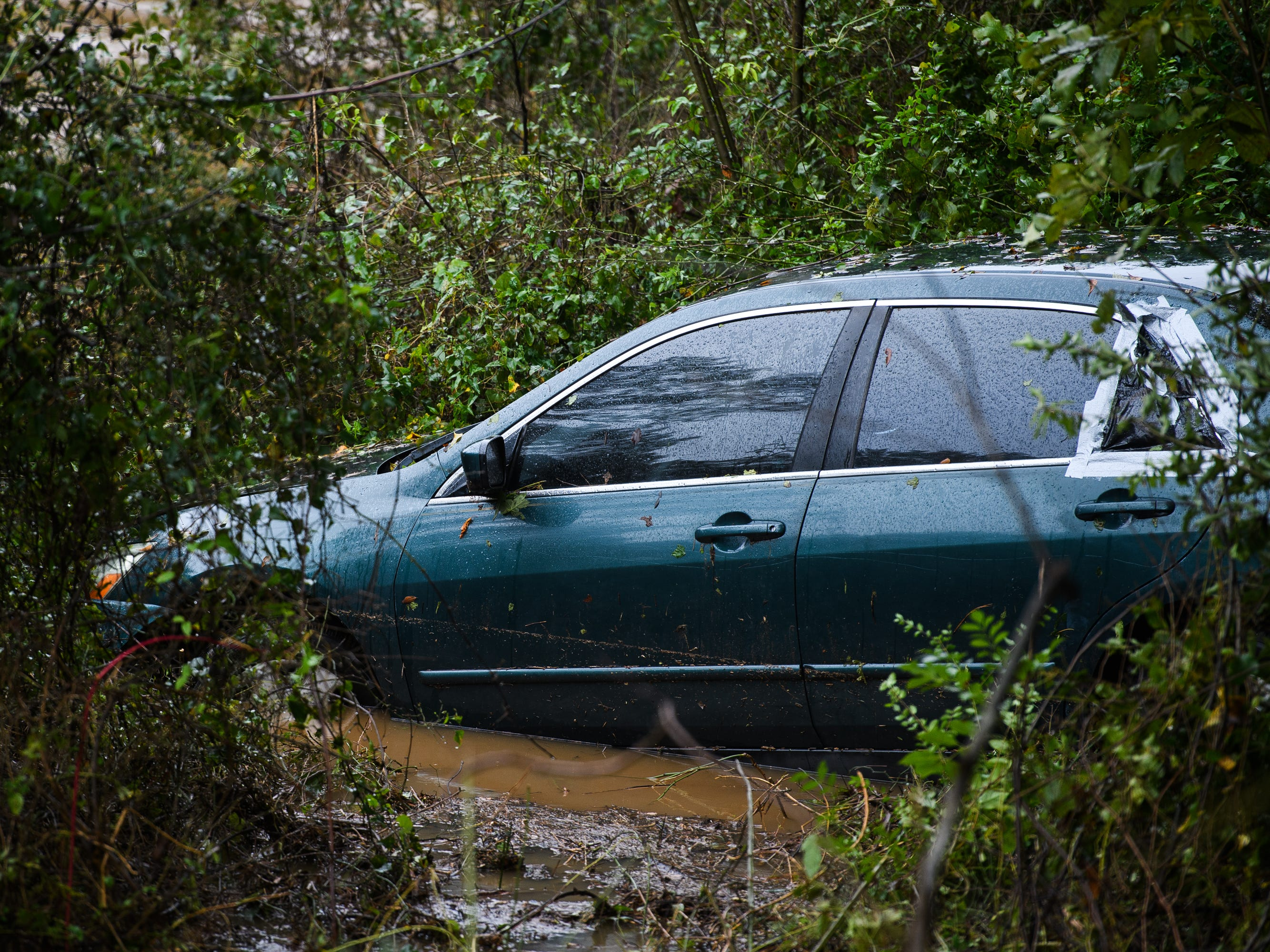 A vehicle is partially submerged in the Reedy River along Parkins Mills Road on Thursday, Oct. 11, 2018.