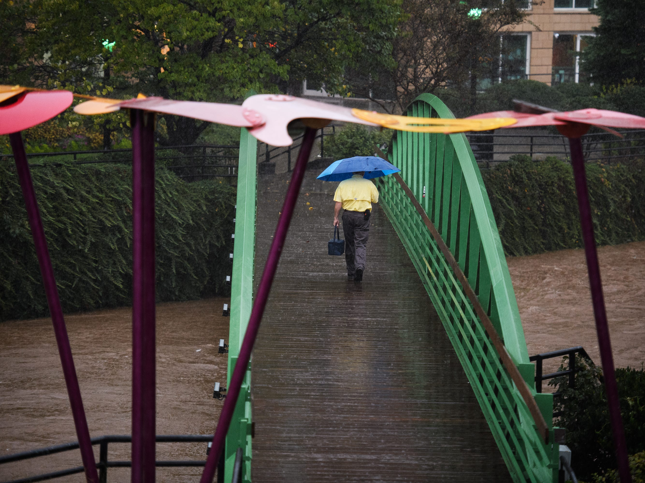 A man walks across the Eugenia Duke Bridge as Tropical Storm Michael hits the Greenville area on Thursday, Oct. 11, 2018.