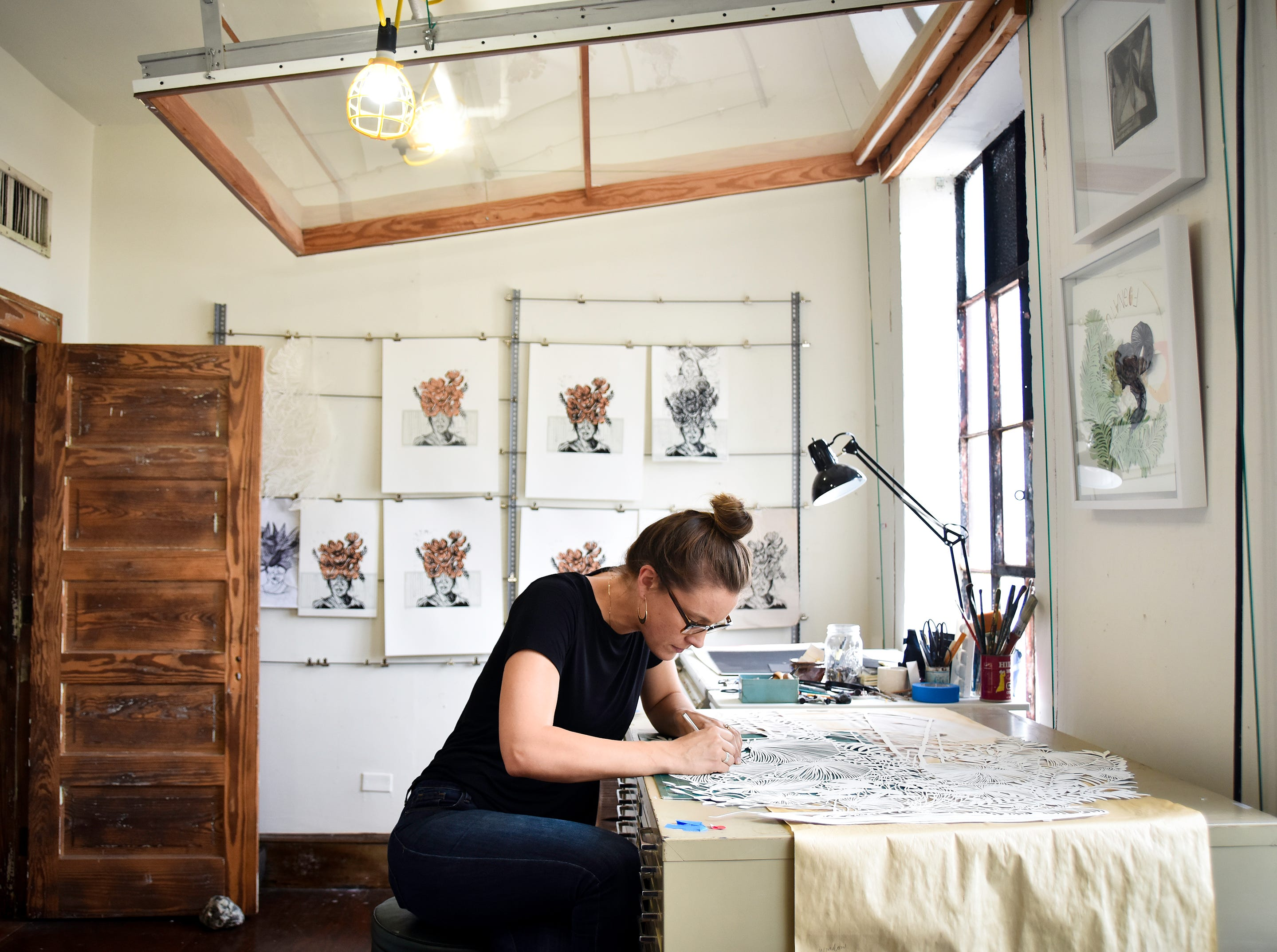 Artist Elizabeth Speaker cuts a design into paper with an X-ACTO knife in her space at Art Bomb Studios in the West Village of Greenville.